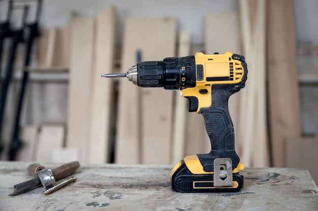 Un tournevis noir et jaune moderne sur une table en bois, des outils en atelier