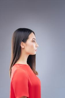 Tournez à gauche. sérieuse belle jeune femme vêtue d'une belle robe rouge et debout contre le mur bleu tout en étant photographiée pour le passeport international