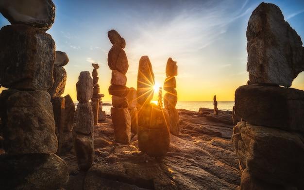 Les tours de pierre sur l'île de samed en thaïlande avec le lever du soleil sur la plage.