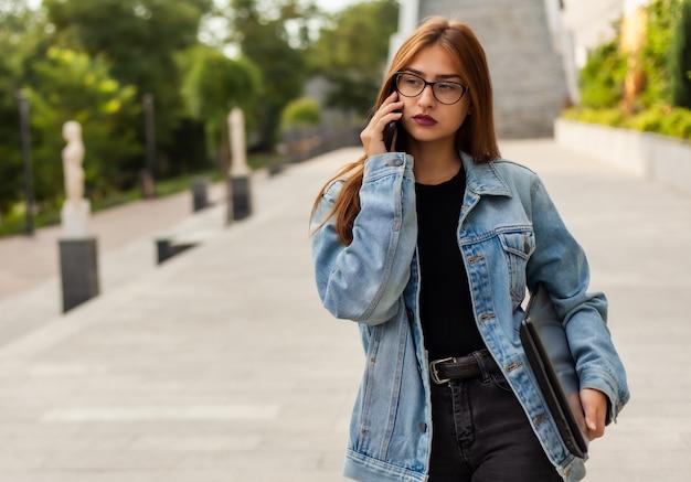 Tout en affaires. jeune femme élégante dans une veste en jean et des lunettes tenant un ordinateur portable et parler au téléphone tout en marchant sur la ville.