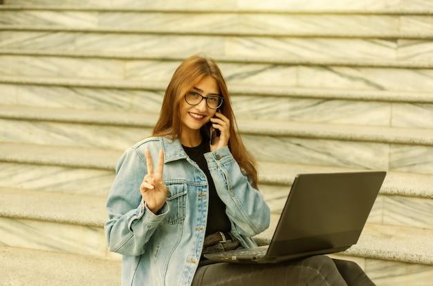 Tout en affaires. jeune femme élégante dans une veste en jean et des lunettes utilise un ordinateur portable et parle au téléphone tout en étant assise dans les escaliers de la ville. travail à distance.