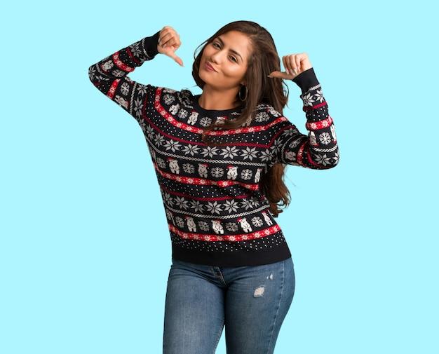 Tout le corps jeune femme portant un maillot de noël pointant les doigts, exemple à suivre