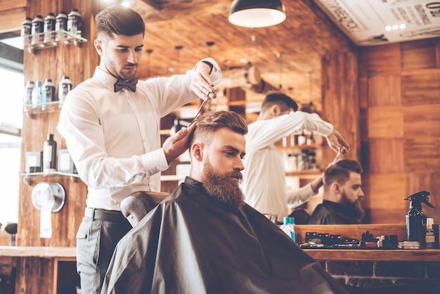 Tout doit être parfait. vue latérale d'un jeune homme barbu se faisant couper les cheveux par un coiffeur assis sur une chaise au salon de coiffure