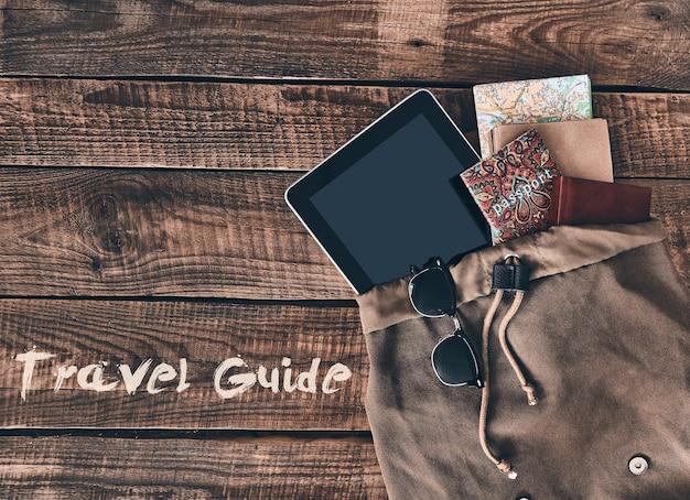 Tout ce dont vous avez besoin. capture en grand angle du passeport de la tablette numérique et de la carte dans le sac