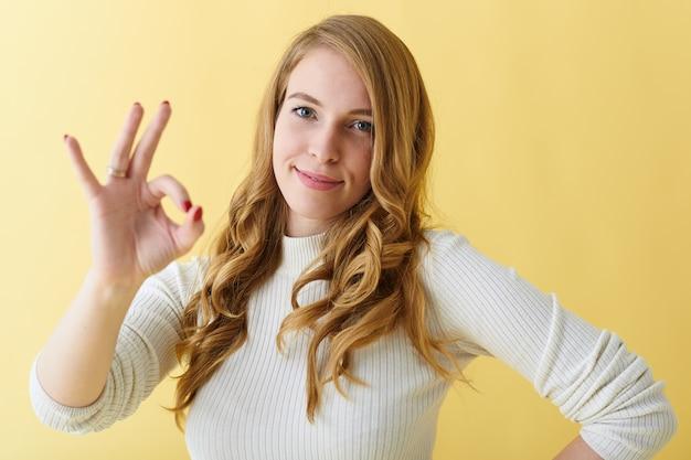 Tout est bon. émotions positives, signes et langage corporel. jolie jeune femme à la recherche amicale souriant joyeusement et faisant un geste correct, approuvant une bonne idée ou aimant un délicieux dîner