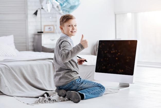 Tout est bon. heureux joyeux gentil garçon vous regarde et montrant le signe ok alors qu'il était assis devant l'écran numérique
