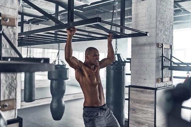 Tout est possible. beau jeune homme africain faisant des tractions tout en faisant de l'exercice dans la salle de sport