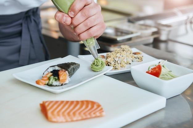 Tout est question de bonne nourriture en gros plan sur les mains du chef préparant de la nourriture japonaise