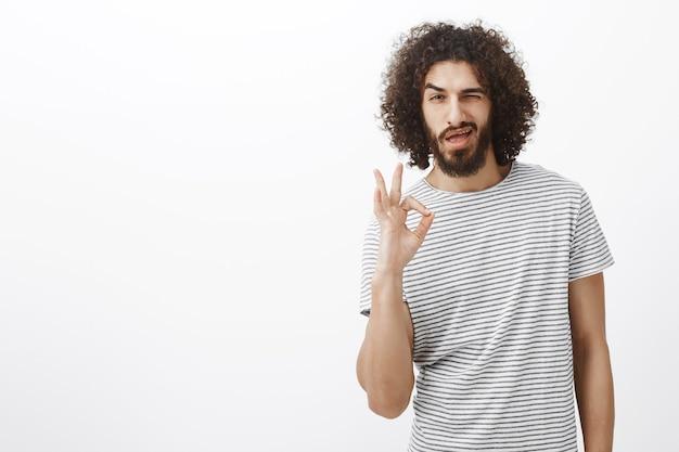 Tout est sous contrôle bébé. bel homme hispanique confiant avec barbe et coiffure frisée, montrant un signe ok ou ok, un clin de œil