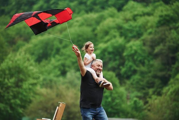 Tout le monde est content. courir avec cerf-volant rouge. enfant assis sur les épaules de l'homme. s'amuser