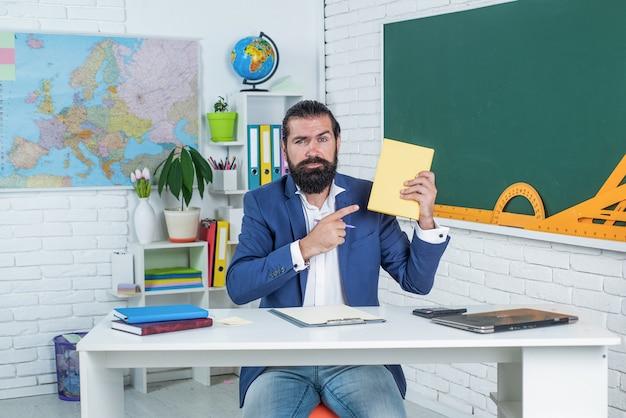 Tout le monde est un performant. passer l'examen. apprendre le sujet. homme sérieux avec barbe regarde le cahier. difficultés à étudier. éducation informelle. un étudiant est assis dans une salle de classe pendant la leçon.