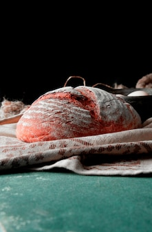 Tout le pain traditionnel rond avec de la farine sur le dessus sur une serviette rustique brune sur une table en pierre.