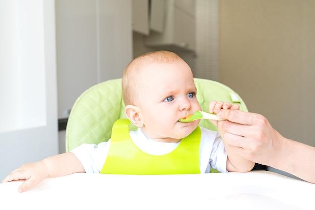 Tout-petit assis sur une chaise haute et mange