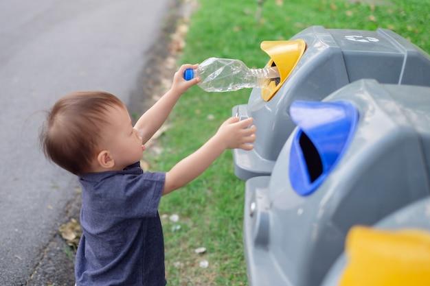 Tout-petit bébé garçon enfant jetant une bouteille en plastique dans la poubelle de recyclage au parc public