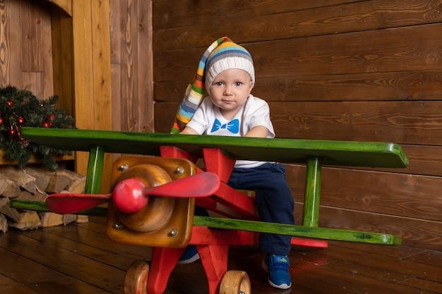 Tout-petit bébé garçon joue dans un grand avion en bois.