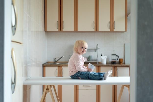 Tout-petit est assis sur la table de la cuisine et attend maman. petit déjeuner à la maison.