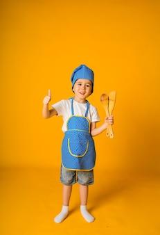 Tout-petit garçon en costume de chef tient des cuillères en bois et montre la classe sur une surface jaune avec un espace pour le texte