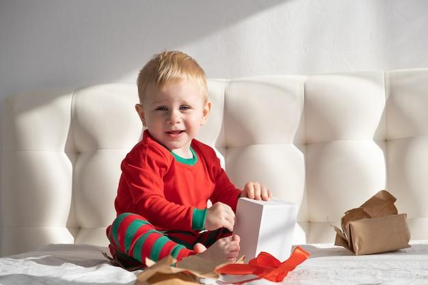 Tout-petit garçon en costume rouge ouverture boîte-cadeau assis sur un lit blanc à la maison.