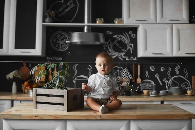 Tout-petit garçon dans une chemise blanche et un short à côté alors qu'il était assis sur la table de cuisine