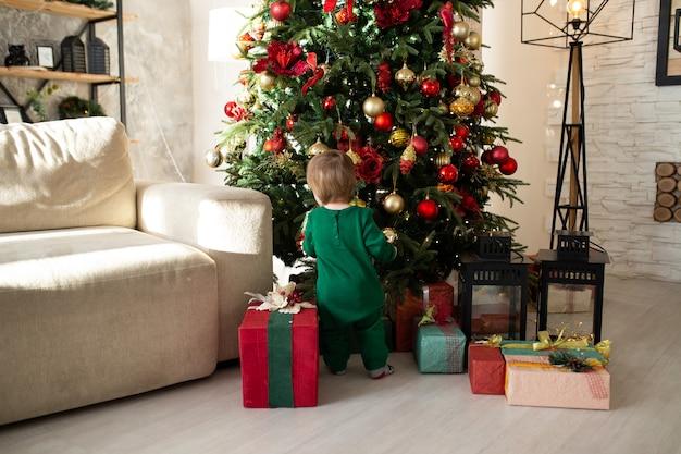 Tout-petit garçon jouant avec des coffrets cadeaux de noël