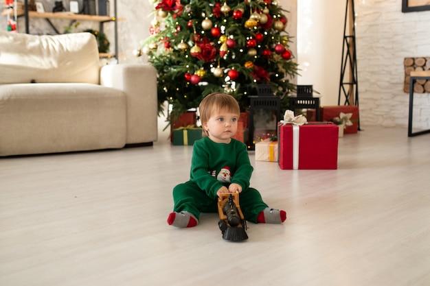 Tout-petit garçon jouant avec train jouet, arbre de noël et coffrets cadeaux