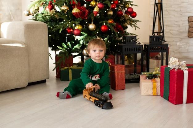Tout-petit garçon jouant avec train jouet, arbre de noël