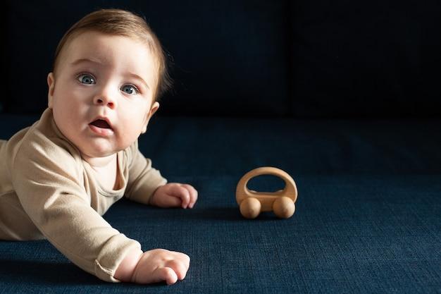 Tout-petit garçon nouveau-né en body beige joue avec vue de côté de jouet en bois