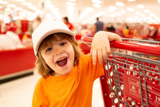 Tout-petit garçon avec panier en supermarché