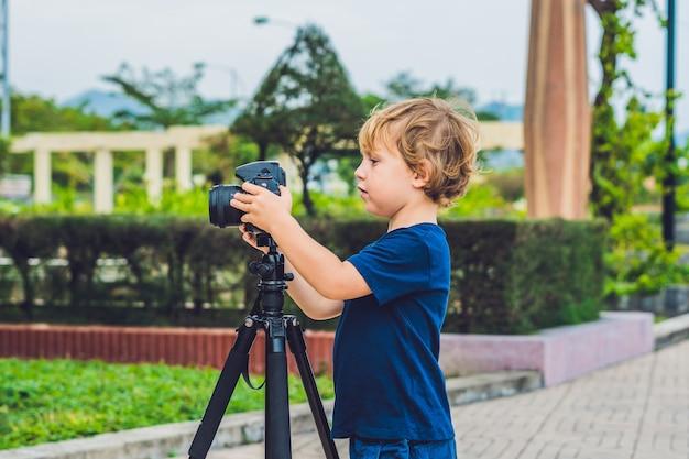 Le tout-petit garçon prend des photos sur un appareil photo sur un trépied