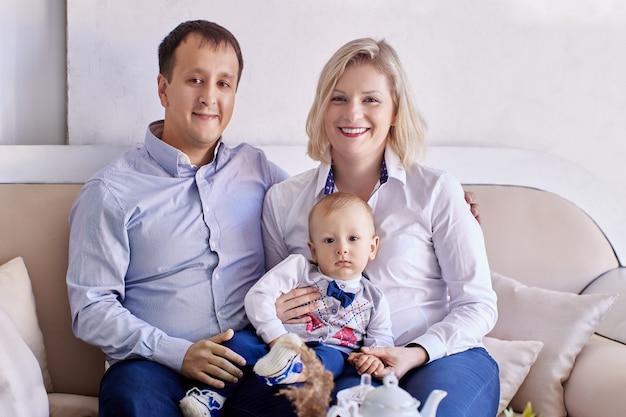 Tout-petit avec la mère et le père souriant s'asseoir sur le canapé dans le salon