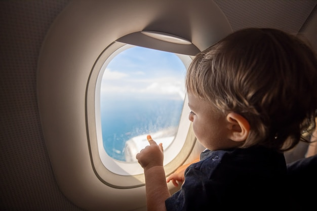 Tout-petit regarde le sol à travers le hublot d'un avion en vol. voyager avec des enfants