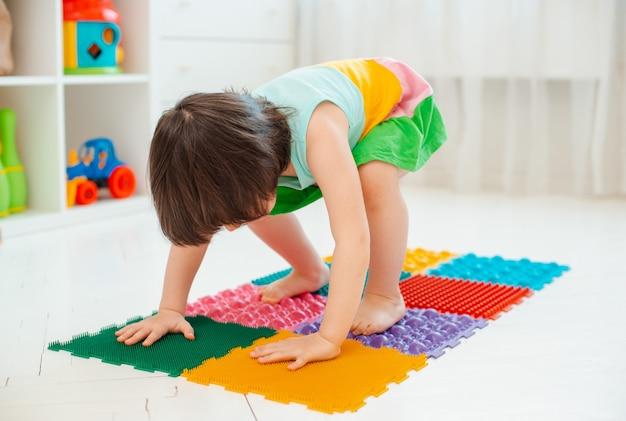 Tout-petit sur le tapis de massage des pieds de bébé. exercices pour les jambes sur un tapis de massage orthopédique. prévention des pieds plats et de l'hallux valgus