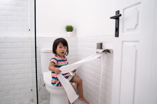 Tout-petit tirant du papier toilette