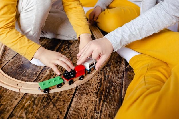 Les tout-petits garçons construisant des chemins de fer et jouant avec un train en bois assis sur le sol dans le salon. petits garçons jouant avec une petite voiture. les enfants jouent.