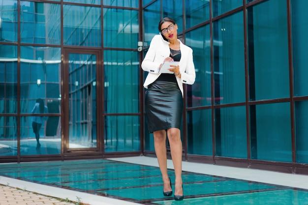 Tout en travail. jeune femme d'affaires afro parler au téléphone et écrire des informations importantes dans le cahier