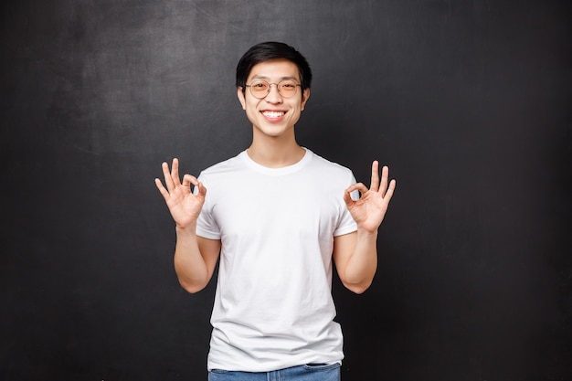 Tout va bien, je vous le garantis. détendu heureux souriant jeune homme asiatique montrant des signes corrects comme assurer que tout s'est bien passé, le travail s'est bien passé, note un excellent produit, garantie de qualité