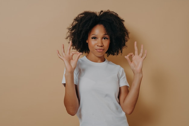 Tout va bien. jeune femme afro-américaine confiante en t-shirt blanc gardant les deux mains dans un geste correct, faisant signe ok tout en se tenant isolée sur fond marron en studio