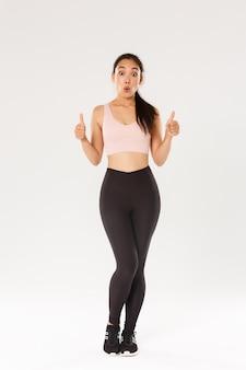 Toute la longueur d'une athlète féminine émerveillée et impressionnée en vêtements de sport, montrant son approbation et l'air émerveillée.