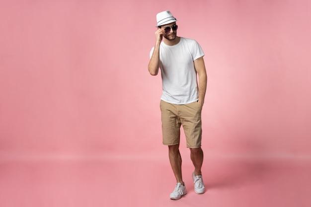 Sur toute la longueur de l'attrayant jeune homme confiant au chapeau debout avec les mains dans les poches.