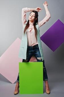 Toute la longueur de la belle fille, avec un panneau publicitaire blanc, sur fond gris et bannière rose et violette