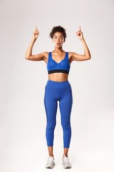 Toute la longueur d'une belle fille de remise en forme étonnée en soutien-gorge de sport bleu et leggings, pointant les doigts vers le haut