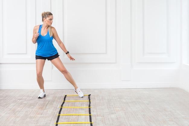 Toute la longueur de la belle jeune femme blonde athlétique sportive en short noir et haut bleu est un entraînement cardio avec des sangles de vitesse au sol et une formation sur des exercices d'échelle d'agilité dans la salle de sport. intérieur, tourné en studio