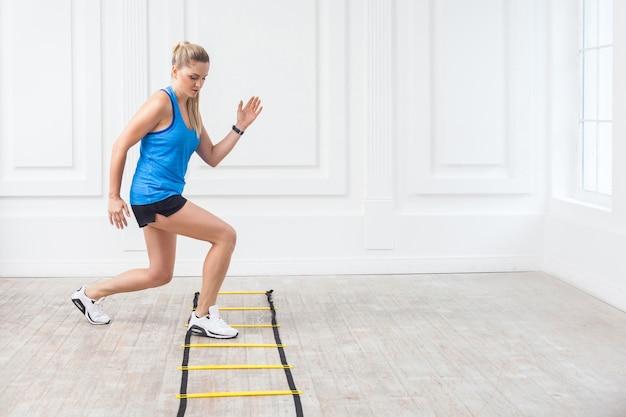 Toute la longueur de la belle jeune femme blonde sportive en short noir et haut bleu travaille dur et s'entraîne sur des exercices d'échelle d'agilité dans la salle de sport. concept d'intérieur, de prise de vue en studio, d'entraînement et de sport.
