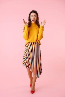 Sur toute la longueur d'une belle jeune femme excitée portant des vêtements colorés isolés sur rose