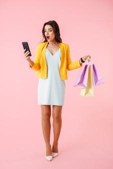 Sur toute la longueur d'une belle jeune femme portant des vêtements colorés debout isolé sur rose, portant des sacs à provisions, tenant un téléphone mobile