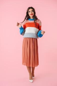 Sur toute la longueur d'une belle jeune femme portant des vêtements colorés debout isolé sur rose, posant