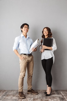 Toute la longueur d'un couple d'affaires asiatique heureux travaillant avec des documents