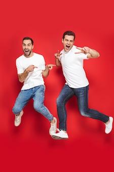 Toute la longueur de deux amis hommes joyeux et excités portant des t-shirts vierges sautant isolés sur un mur rouge, célébrant