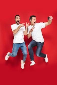 Toute la longueur de deux amis hommes joyeux et excités portant des t-shirts vierges sautant isolés sur un mur rouge, prenant un selfie