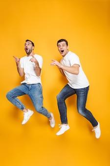 Toute la longueur de deux amis joyeux et excités portant des t-shirts vierges sautant isolés sur un mur jaune, pointant du doigt